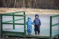 Two little brothers playing, on autumn landscape, sitting and smiling the wooden pier near frozen lake Royalty Free Stock Photo