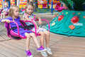Two little cute sisters ride on carousel in the fashion lovely park Royalty Free Stock Photos