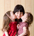 Two little daughter kiss their mother Stock Images