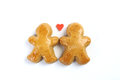 Two little fallen in love gingerbread figure and in between two little figure is one red sweet heart on white background Royalty Free Stock Images