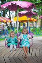 Two little fashion lovely sisters ride on the carousel in park this image has attached release Stock Photography