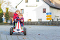 Two little friends kids in red jackets driving fast race car tog