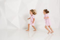 Two little funny and laughing girl in gently pink dresses playing in white studio