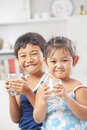 Two little girl and boy each holding glass of milk Royalty Free Stock Photos