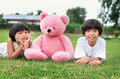 two Little girl with teddy bear and smile on grass Royalty Free Stock Photo