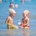 Two little girls with bandana playing in the sea. Royalty Free Stock Photo