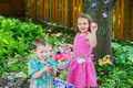 Two little girls and a boy with their easter eggs in dresses hold basket colorful during family day celebration egg hunt activity Stock Image