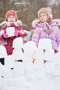 Two little girls build wall from snow blocks in winter park Stock Photos