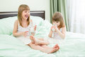 Two little girls drinking milk on bed from glasses Stock Images