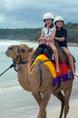 Two little girls enjoying a camel ride on the beach Stock Photo