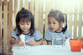 Two little girls having fun to paint on stucco doll Royalty Free Stock Photo