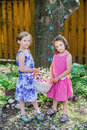 Two little girls holding an easter basket cute together in dresses with smiles a with flowers and colorful eggs in the spring Stock Photos