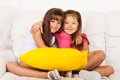 Two little girls hugging with pillows happy asian and caucasian together and sitting pillow on the white leather coach in living Royalty Free Stock Image
