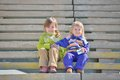 Two little girls on a ladder sisters sitting stairway outdoor Stock Images