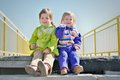 Two little girls on a ladder sisters sitting stairway outdoor Royalty Free Stock Images