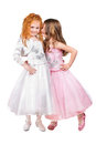 Two little girls in nice dresses whispering isolated on white Royalty Free Stock Images