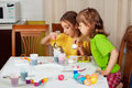Two little girls painting Easter eggs Stock Photos