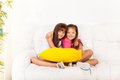 Two little girls with pillows happy asian and caucasian calm and relaxed years old sitting and hugging holding pillow on the white Stock Image