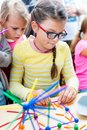 Two little girls playing with lots of colorful plastic sticks ki Royalty Free Stock Photo