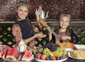 Two little girls playing mandolin and dancing dressed in central asian clothes during breakfast at chaikhana uzbekistan Royalty Free Stock Photos