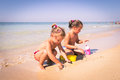 Two little girls playing with sand near the crystal clear sea. Royalty Free Stock Photo