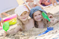 Two little girls playing in the sand Royalty Free Stock Photo