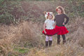 Two little girls posing in the countryside portrait of charming dressed retro style with flowers their hair and frilly red skirts Stock Image
