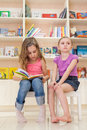 Two little girls are reading an interesting book in the library focus on right girl Stock Photography