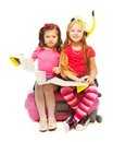 Two little girls ready for vacation cute exited sitting on suitcase with map preparing to travel wearing snorkel and mask isolated Royalty Free Stock Image