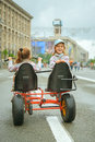 Two little girls riding toy cycle on streets of city Royalty Free Stock Photography