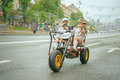 Two little girls riding toy cycle on streets of city Royalty Free Stock Photos