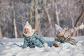 Two little girls sit in snowdrift and make faces in winter Royalty Free Stock Photo