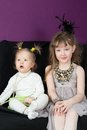 Two little girls sitting on the black sofa in fashionable clothes Royalty Free Stock Photography