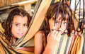 Two little girls sitting in the hammock on the beach are Royalty Free Stock Photos