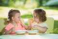 Two little girls sitting at a table and eating together against green lawn