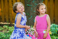 Two little girls smiling and holding an easter basket cute together in dresses a with flowers colorful eggs in the spring season Royalty Free Stock Images