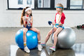 Two little girls in sportswear sitting at fitness studio Royalty Free Stock Photo