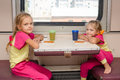 Two little girls on train sitting at the table in the outboard second-class car in the same clothes Royalty Free Stock Photo