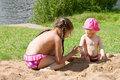 Two little girls, two sisters playing in the sand on the beach Royalty Free Stock Photo