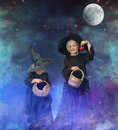 Two little halloween witches at night with stars and moon background space Royalty Free Stock Photography