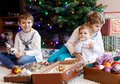 Two little kid boys and adorable baby girl decorating Christmas tree with old vintage toys and balls. Royalty Free Stock Photo