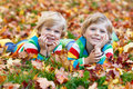 Two little kid boys laying in autumn leaves in colorful clothing Royalty Free Stock Photo