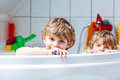 Two little kids boys playing together in bathtub Royalty Free Stock Photo