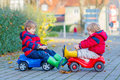 Two little kids boys playing with toy cars, outdoors