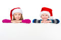 Two little kids in santa claus hats resting on white board smiling camera over poster isolated background Stock Photo