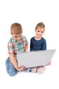 Two little kids using a laptop on the white Stock Photos