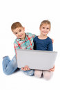 Two little kids using a laptop on the white Stock Photo