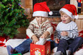 Two little sibling boys being happy about christmas present indoor with decoration Stock Photos