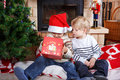Two little sibling boys being happy about christmas present indoor with decoration Stock Images
