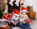 Two little sibling boys being happy about christmas present playing with toys indoor with decoration Royalty Free Stock Images